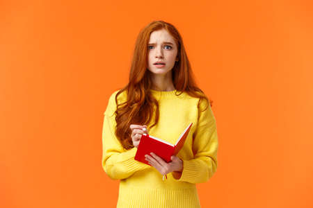 Concerned tensed attractive redhead female student cant write down everything from blackboard after lector, biting lip look troubled and perplexed, holding red notebook and pen, orange background