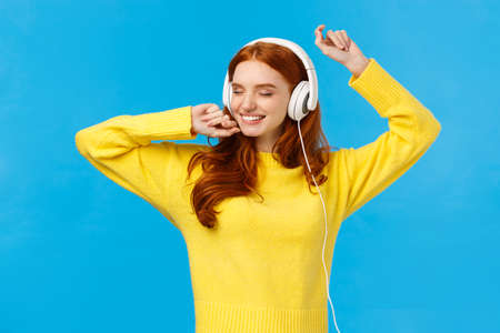 Carefree charming redhead female in yellow sweater, dancing relaxed and joyful with hands lifted up, close eyes and smiling happy, listen music headphones, standing blue background