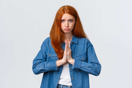 Waist-up portrait gloomy cute redhead girl begging aplogy, press hands together in pray, pouting and looking camera pleading, asking help, sorry, feeling regret for causing mess, white background