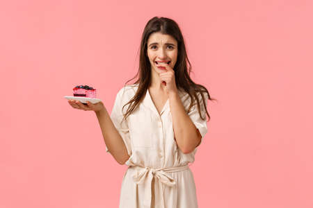 Maybe just one bite. Tempting and eager brunette woman want try tasty piece cake, holding dessert frowning and biting fingernails from desire to eat sweets, resist trying stick diet, pink background