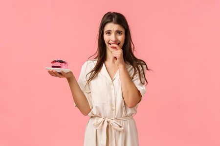 Vielleicht nur ein Bissen. Verlockende und eifrige brünette Frau möchte leckeren Stückkuchen probieren, Dessert runzeln und Fingernägel beißen aus dem Verlangen, Süßigkeiten zu essen, widerstehen, Stickdiät zu versuchen, rosa Hintergrund Standard-Bild