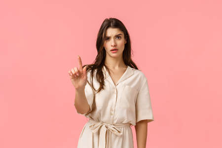 Not so fast, I disagree. Displeased and disappointed serious-looking pissed caucasian girlfriend shaking finger in disapproval and negaitve reply, give warning, standing pink background