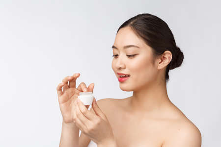 Beautiful young woman on white isolated background holding cosmetic face cream, asian