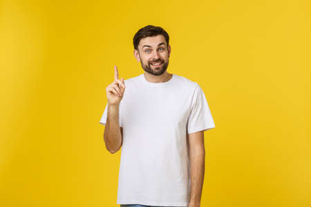 Young happy man gets good idea, raises fore finger as going to voice it, being glad have genius thoughts in mind, isolated over white background.