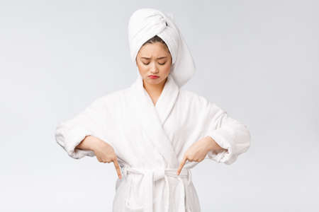Young beautiful woman wearing shower towel after bath over isolated white background pointing with finger.