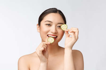 Natural homemade fresh cucumber facial eye pads facial masks. Asian woman holding cucumber pads and smile relax with natural homemade Reklamní fotografie