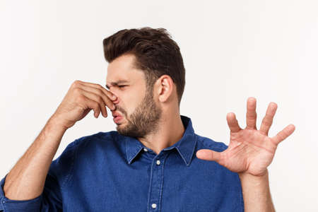 Man holding his nose against a bad smell isolated over grey background.