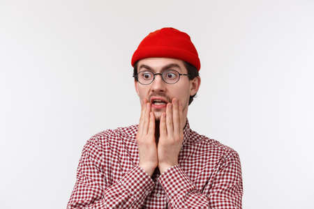 Oh gosh omg. Surprised and speechless hipster guy with beard in red beanie, glasses, gasping staring at something shocking gross, look left spot terrible thing, standing white background