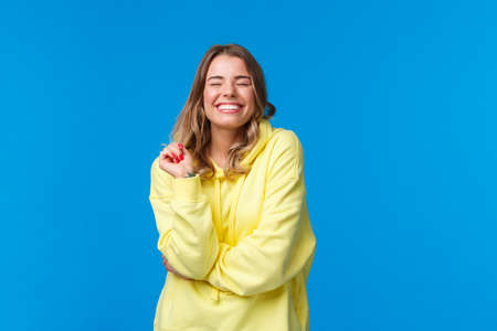 Cheerful carefree pleased girl feel happy and delighted, close eyes dreamy smiling with perfect beaming grin, touch strand of hair, standing in yellow hoodie over blue background