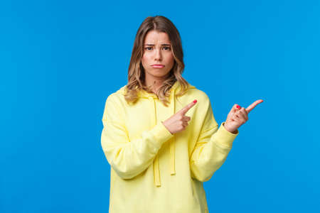 Upset and gloomy cute blond teenage girl frowning and sulking from unfair situation, someone offended her, feel jealous or regret, frowning camera and pointing fingers right, blue background Stock Photo