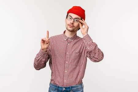 Waist-up portrait of smart and snobbish man patronising someone, scolding someone or correct person, raise one finger adding his opinion, fixing glasses on face,s tand white background Standard-Bild