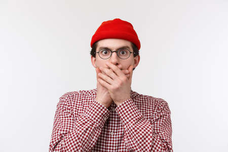 Close-up portrait of shocked young man heard something unbelievable and shook, close mouth with hands stare at camera as if gossiping about concerning thing, standing white background