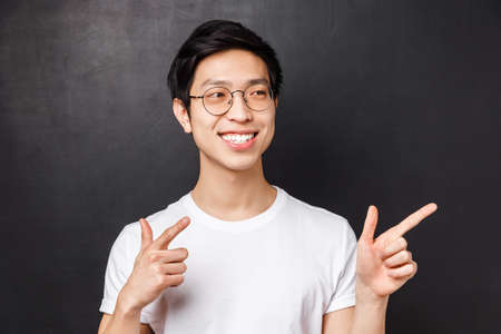 Close-up portrait of good-looking asian man in white t-shirt and glasses, spot friend on other side of room, pointing finger pistols at right side, smiling saying hi, informal greeting concept
