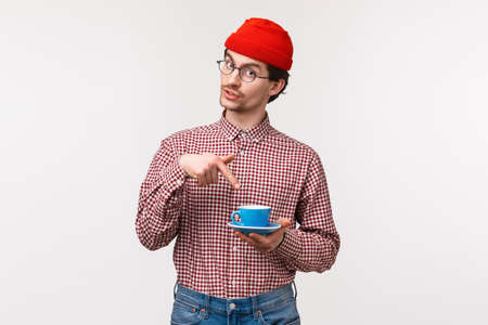 Want some. Friendly-looking funny young hipster bearded guy in red beanie and glasses, suggest coworker cup of coffee, pointing at his tea as asking for refill, standing white background