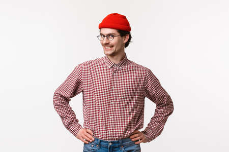 Waist-up portrait upbeat and enthusiastic young hipster guy in red beanie and glasses, with checked shirt, standing ready with confident straight pose, hold hands on waist and smiling camera