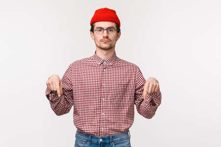 Waist-up portrait serious-looking determined young man in checked shirt, red beanie and glasses looking strict camera as pointing fingers down as something important and worth attention Imagens