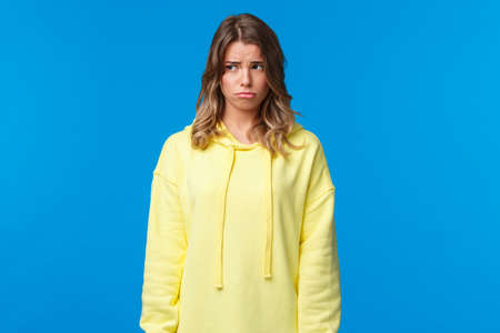 Gloomy and lonely say caucasian girl looking away, sobbing childish and sulking as feeling uneasy, being let down, having bad day at university, standing upset over blue background