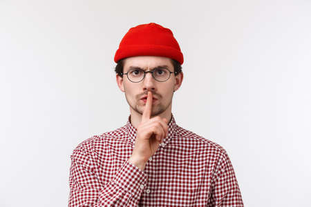 Serious angry bearded caucasian man shushing at camera disappointed and pissed-off with disobedient students talking too loud, make hush gesture with index finger pressed lips, frowning, keep quiet