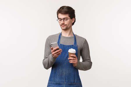 Portrait of carefree handsome young male student working part-time in restaurant in apron, have lunch break, using mobile phone and drink coffee form take-away cup, white background