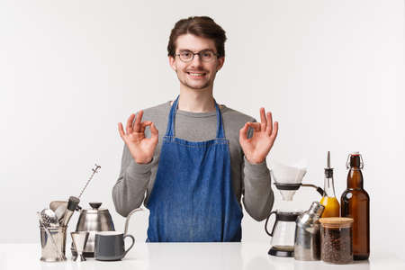 Barista, cafe worker and bartender concept. Portrait of satisfied, pleased young male employee in apron smiling assuring, guarantee you will like coffee, making cappuccino show okay sign 版權商用圖片
