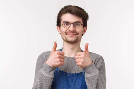 Close-up portrait of cheerful enthusiastic male employee agrees with coworker, show thumbs-up and smiling pleased, give approval, guarantee best quality of coffee, stand white background 版權商用圖片