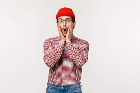 Surprised startled and fascinated young funny bearded guy in red beanie react to overwhelming shocking news, hear something concerning, stare with disbelief and amazement, touch cheeks