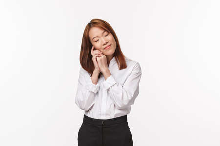 Portrait of tender and dreamy, romantic asian woman thinking about something silly, close eyes and touch cheek lean on hand dreaming about vacation with boyfriend, white background