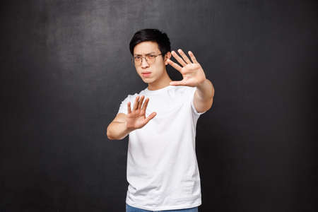 Serious-looking annoyed and displeased asian guy telling stop it, cover face with hands as if defending himself from glimmering light, squinting bothered with too bright lamp, black background