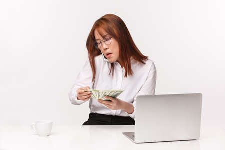 Career, work and women entrepreneurs concept. Close-up portrait of busy serious-looking asian businesswoman, office lady sitting table, counting money, talking on mobile phone, writing in laptop