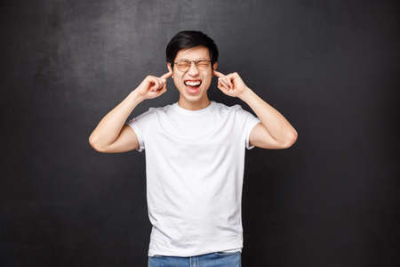 Lifestyle and people concept. Bothered and anguished young asian guy screaming from discomfort and distress as hearing loud noise, close ears with fingers shut eyes disturbed, stand black background Stock Photo