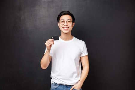 Bank, finance and payment concept. Portrait of satisfied charismatic asian guy in t-shirt and glasses, recommend put money on deposit, pleased with banking service, hold credit card and smiling