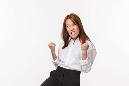 Girl power. Satisfied and pleased asian woman feeling like fighter, winning competition, fist pump and look relieved pleased, achieve goal, become winner, receive prize or reward, white background