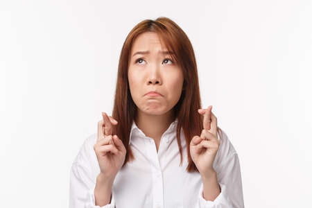 Close-up portrait sad miserable cute asian girl sobbing and looking upset up, making wish, gaze upset, cross fingers good luck, pleading, want something come true, anticipating good result hopeless