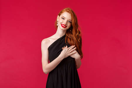 Fashion, luxury and beauty concept. Elegant good-looking redhead woman in black dress, with red lipstick and luxurious outfit, tilt head and smiling thankful, hold hand on heart touched with praises Archivio Fotografico