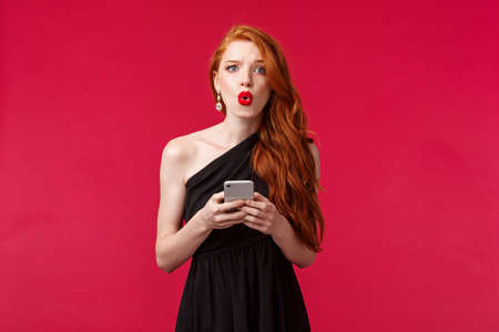 Portrait of concerned and confused young redhead woman being dumped by message on her prom night, look frustrated dont understand what happened, wear black dress, holding smartphone