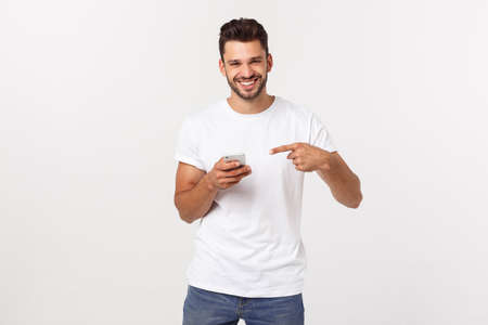 Happy casual man playing on smartphone over gray background Foto de archivo