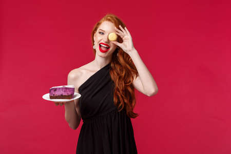 Portrait of gorgeous carefree redhead woman in slim black dress, hold macaron over eye funny smiling and cake on plate, party enjoy celebration of holiday, stand over red background Reklamní fotografie