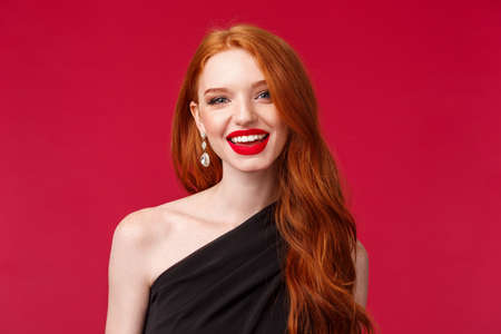 Close-up portrait of feminine gorgeous young redhead caucasian woman in red lipstick, earrings and evening slim black dress, smiling happy and pleased, having conversation with person on party