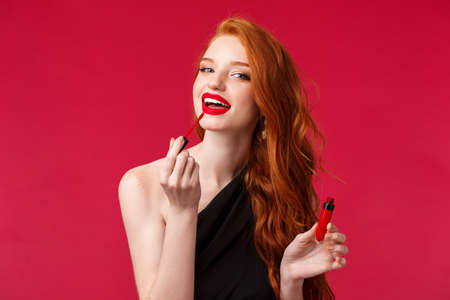 Makeup, beauty and women concept. Close-up portrait beautiful redhead feminine woman applying lipstick, red lip gloss and looking at camera as if in mirror, standing over red background Standard-Bild