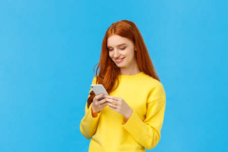 Conversation, messaging and people concept. Redhead cute carefree girl enjoy browsing online, picking new dress internet store, shopping using smartphone, smiling found excellent choice, order