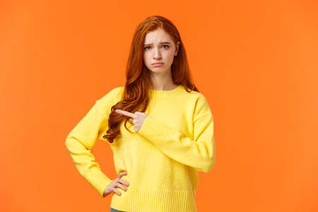 Girl looking upset and unsatisfied. Sad sulky redhead woman pointing left with envy or jealousy cant make it to party, frowning and sulking, showing what she want, standing orange background unhappy