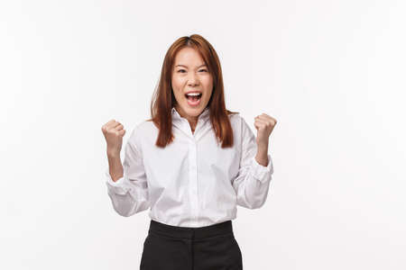 Cheerful successful lucky asian woman winning prize, lottery standing over white background pump fists and scream yes in joy, triumphing over victory, become champion or winner, white background