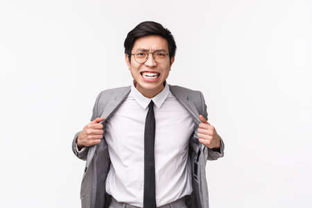 Waist-up portrait of pissed-off, aggressive young asian businessman in grey suit and tie, ripping his clothes from anger, losing patience, distressed standing over white background Stockfoto