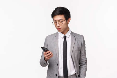 Waist-up portrait of serious-looking handsome stylish businessman in grey suit, hold hand in pocket, casually using mobile phone, texting business partner, using smartphone, white background