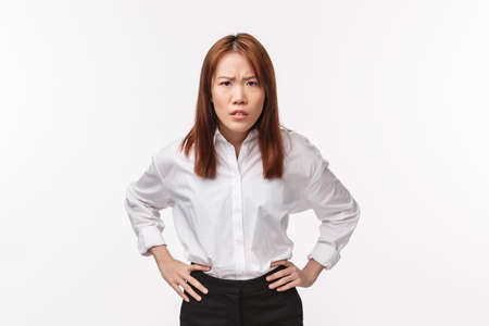 Portrait of disappointed and strict asian woman hold hands on waist and bending forward, frowning look with blame, accuse person being impolite, scolding disobedient employee, white background