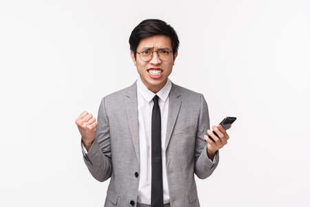 Waist-up portrait of displeased, bothered and annoyed asian businessman in grey suit, clenching teeth and fists, frowning aggressive, grimacing irritated from reading bad news on mobile phone