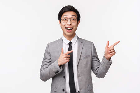 Waist-up portrait of excited and amazed, happy asian businessman in grey suit, showing you something awesome, great advertisement, promo banner on right side of copy space, white background