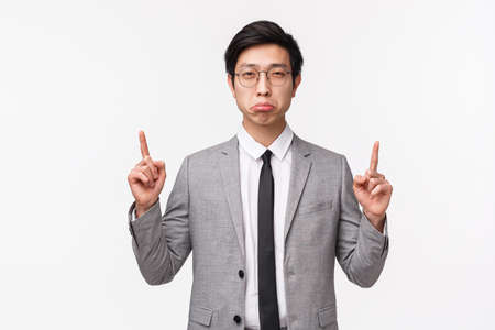 Waist-up portrait of skeptical and suspicious young asian office clerk in gray suit, squinting with disbelief and pouting feeling doubt about person telling truth, pointing fingers up