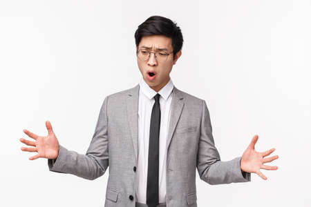 Waist-up portrait of impressed asian young male office clerk in suit, shaping something big, describe large object with stretched hands, open mouth gasping thrilled, standing white background