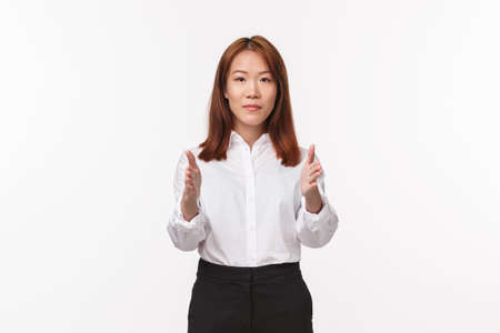Portrait of young elegant asian woman in office clothes, pointing at camera, showing way, female instructor give directions, teaching new flight attendants, standing white background